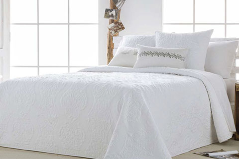 Ropa de cama de matrimonio en color blanco con cojines decorativos